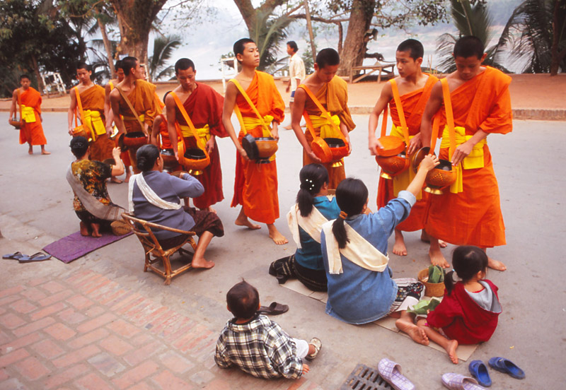 Devout Buddhists offer monks gifts of sticky rice at dawn in Luang Prabang