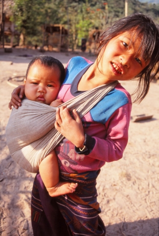 A girl carries her baby brother in Ban Nalan Neua village