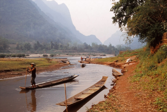 A man punts a boat on the Nam Ou River