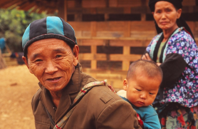 A man carries his grandchild in a Hmong highland village