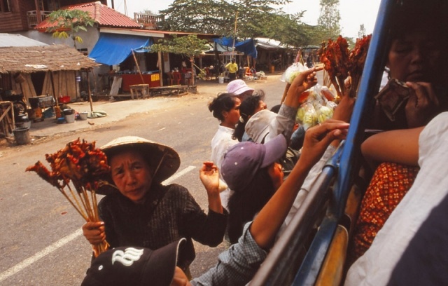 A hawker offers grilled chicken at a bus stop in southern Laos