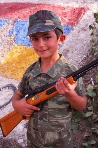 A boy armed with a plastic rifle stands guard over the Armenian flag in Areni