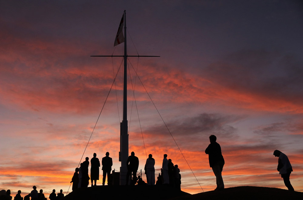 March: The sun rises behind Russell's Flagstaff Hill during commemorations of the 175th anniversary of the Battle of Kororāreka. Photo: Peter de Graaf