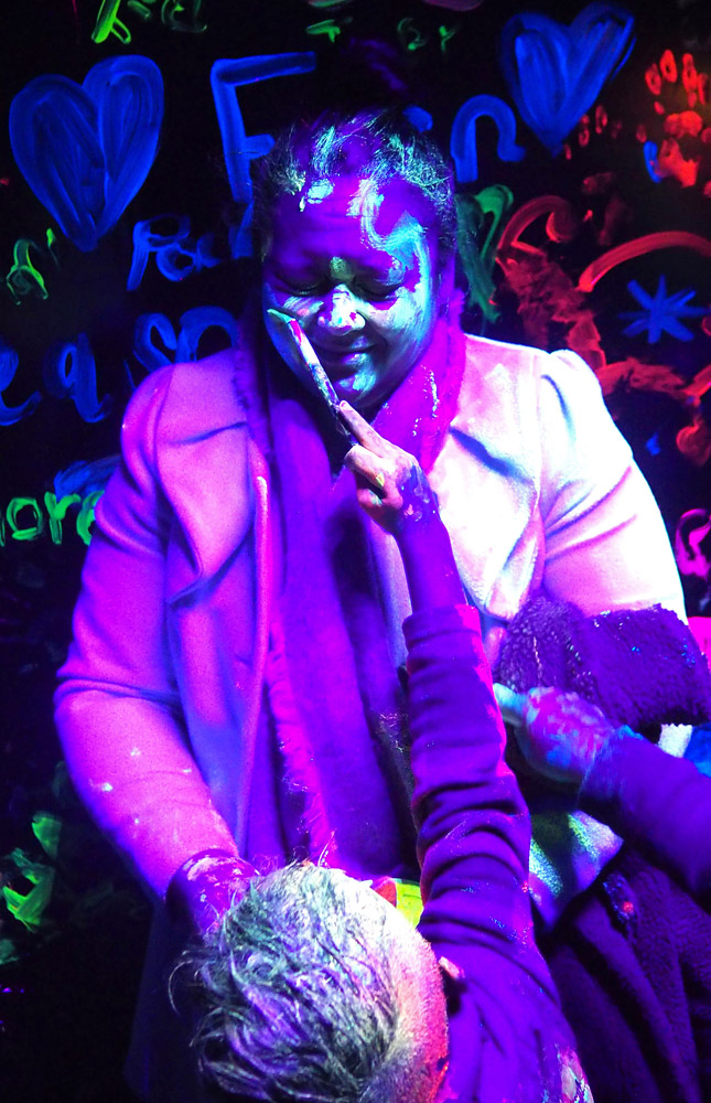 July: Wait, kids! That's not a canvas... Oops, too late. Edina Harris gets a makeover during Bling Bling Toi Marama, a glow-in-the-dark event in Kaikohe. Photo: Peter de Graaf
