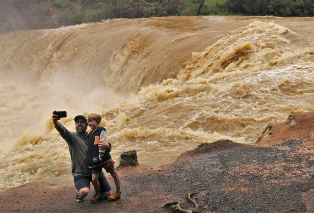July: Hamish Macbeth and son Harrison, 6, grab a selfie at the flooded Haruru Falls near Paihia. Photo: Peter de Graaf