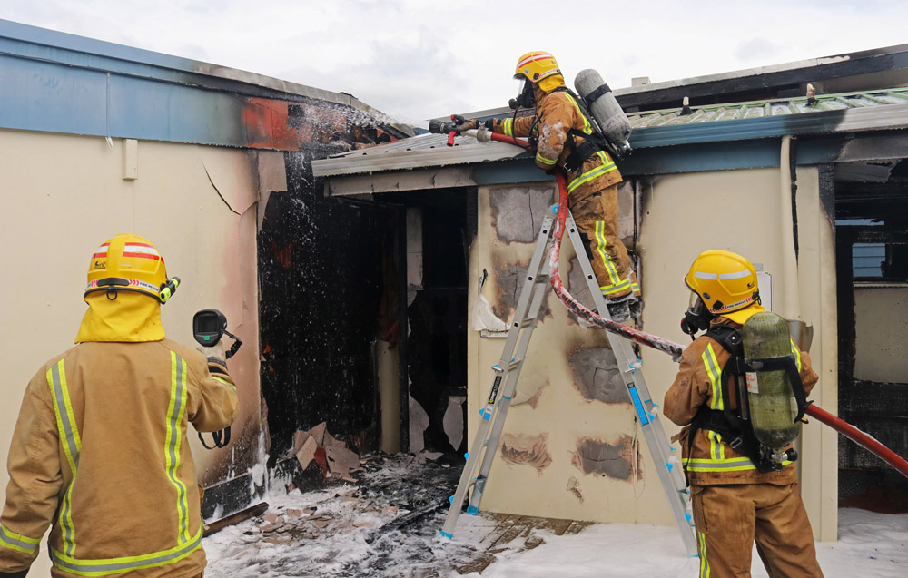 October: Volunteer firefighters hose down a toilet block and check for hotspots during a fire at Kerikeri High School. Photo: Peter de Graaf