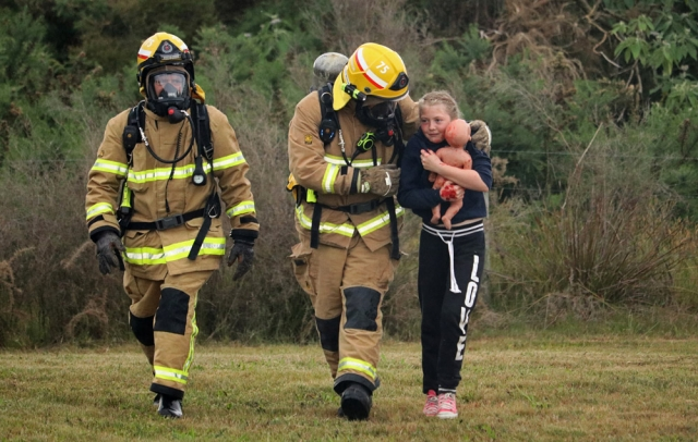 November: Firefighters lead 11-year-old HannahKate to safety during a crash simulation at Bay of Islands Airport in Kerikeri. Photo: Peter de Graaf