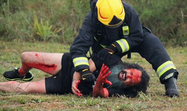 November: Airport firefighter Kyle Hanley tends to actor Willi Henley during a simulated plane crash at Bay of Islands Airport in Kerikeri. Photo: Peter de Graaf
