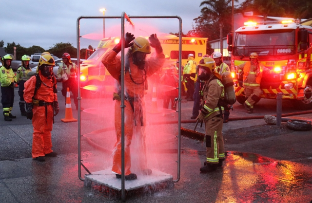 March: Firefighters wash off in a decontamination shower during a chemical spill exercise in Kerikeri. Photo: Peter de Graaf