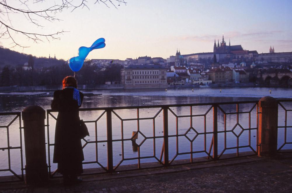 A woman holds a rabbit balloon by the Vltava River, Prague