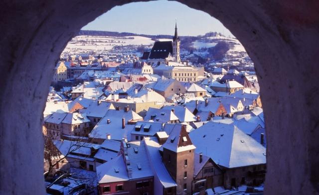 The medieval town of Český Krumlov is framed by a window in the castle garden walls