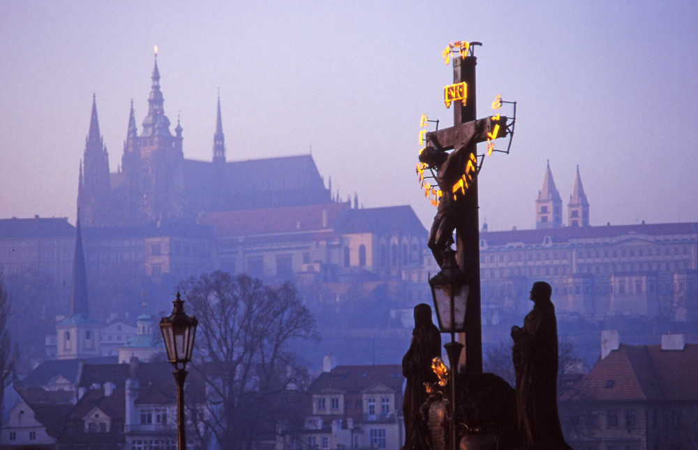 Cross on the 14th century Charles Bridge with Prague Castle in the distance