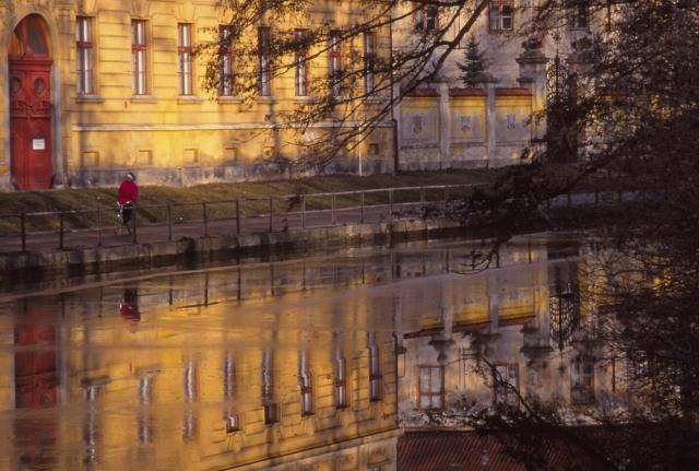 Česká High School is reflected in a partly frozen Malše River, České Budějovice