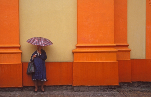 A woman shelters from the rain at the Church of St John of Nepomuk in West Bohemia