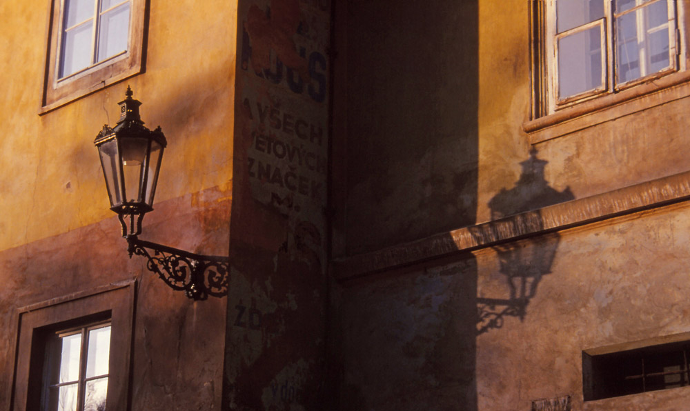 A street lamp casts a shadow on a Prague façade