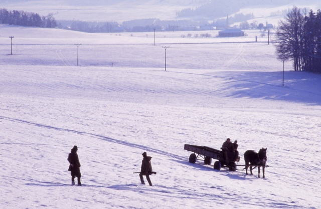 Hunters and a horse-drawn cart in a wintry South Bohemian landscape