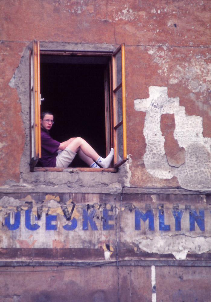 A boy stares from a window in Český Krumlov.
