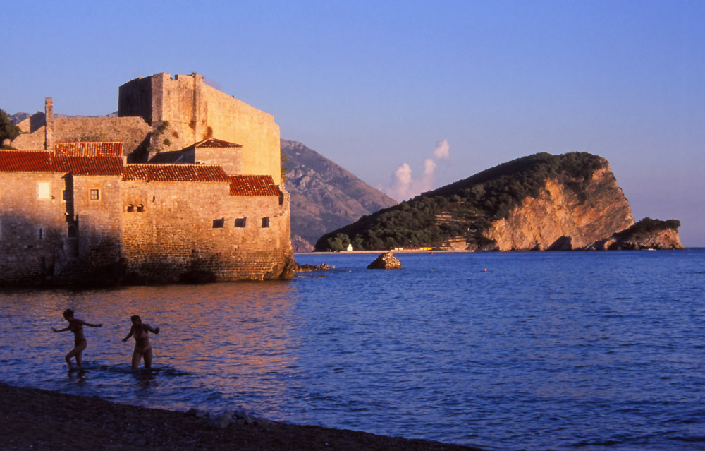 Montenegro, 1999: Swimmers emerge from the sea next to the ancient walled city of Budva