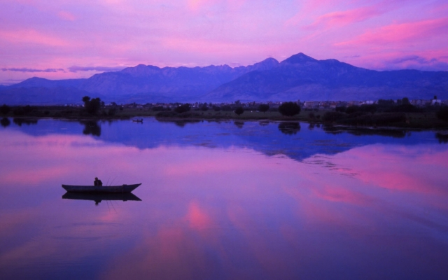A fisherman tries his luck at dusk on Lake Shkodra, largest lake in the Balkans
