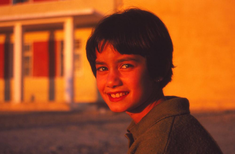Majlinda smiles for a sunset photo outside her school in Krujë