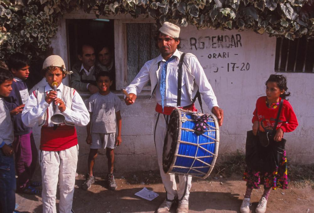 Street musicians perform outside a jeweller's shop in Elbasan