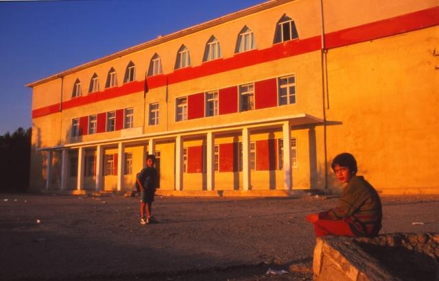 Majlinda waits for her little brother outside the primary school in Krujë