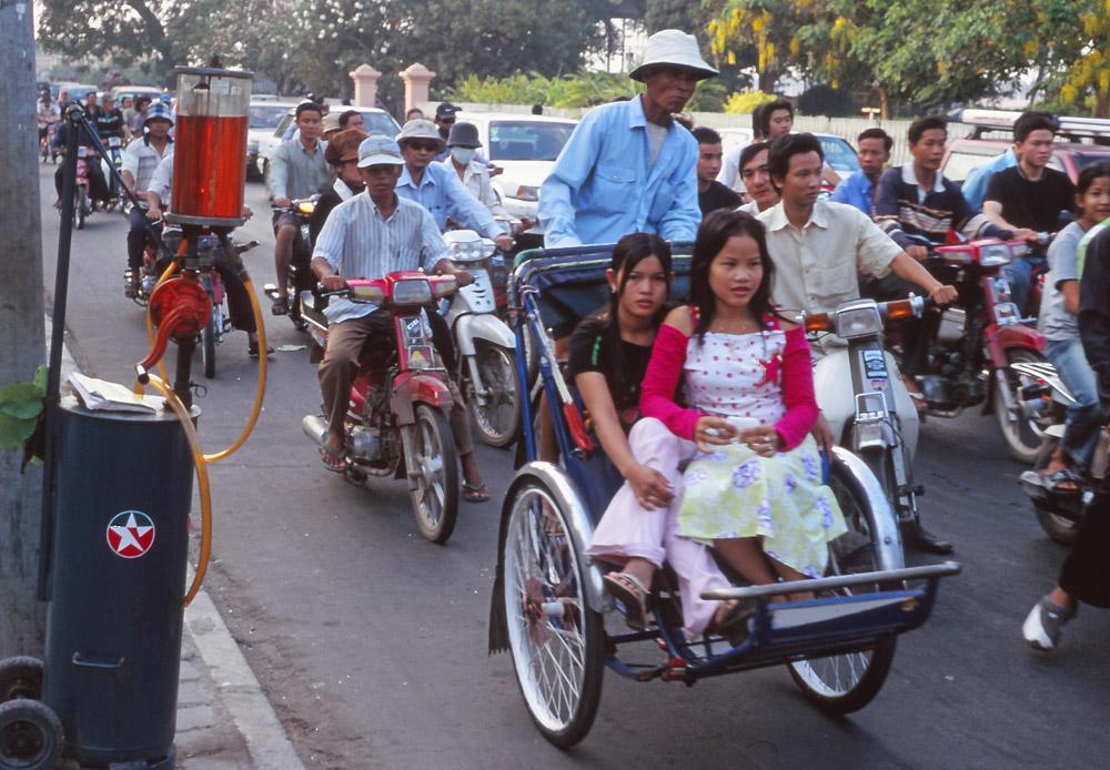 Rush hour in Phnom Penh. Note the hand-operated roadside petrol pump