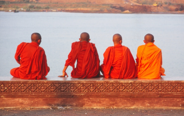 Monks relax by the Tonlé Sap River in Phnom Penh