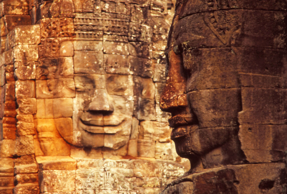 """Two of the 216 giant faces which decorate the 54 towers of the Bayon, a 12th century temple at the centre of Angkor Thom (""""Great City"""")"""