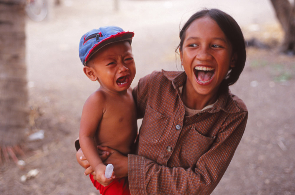 A village boy is terrified by the photographer; his sister not so much
