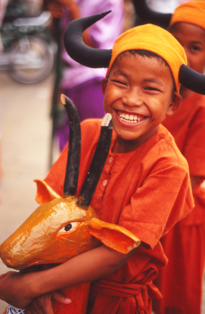 Children perform a dance featuring hunters and animals to bring a luck to a shop in Battambang